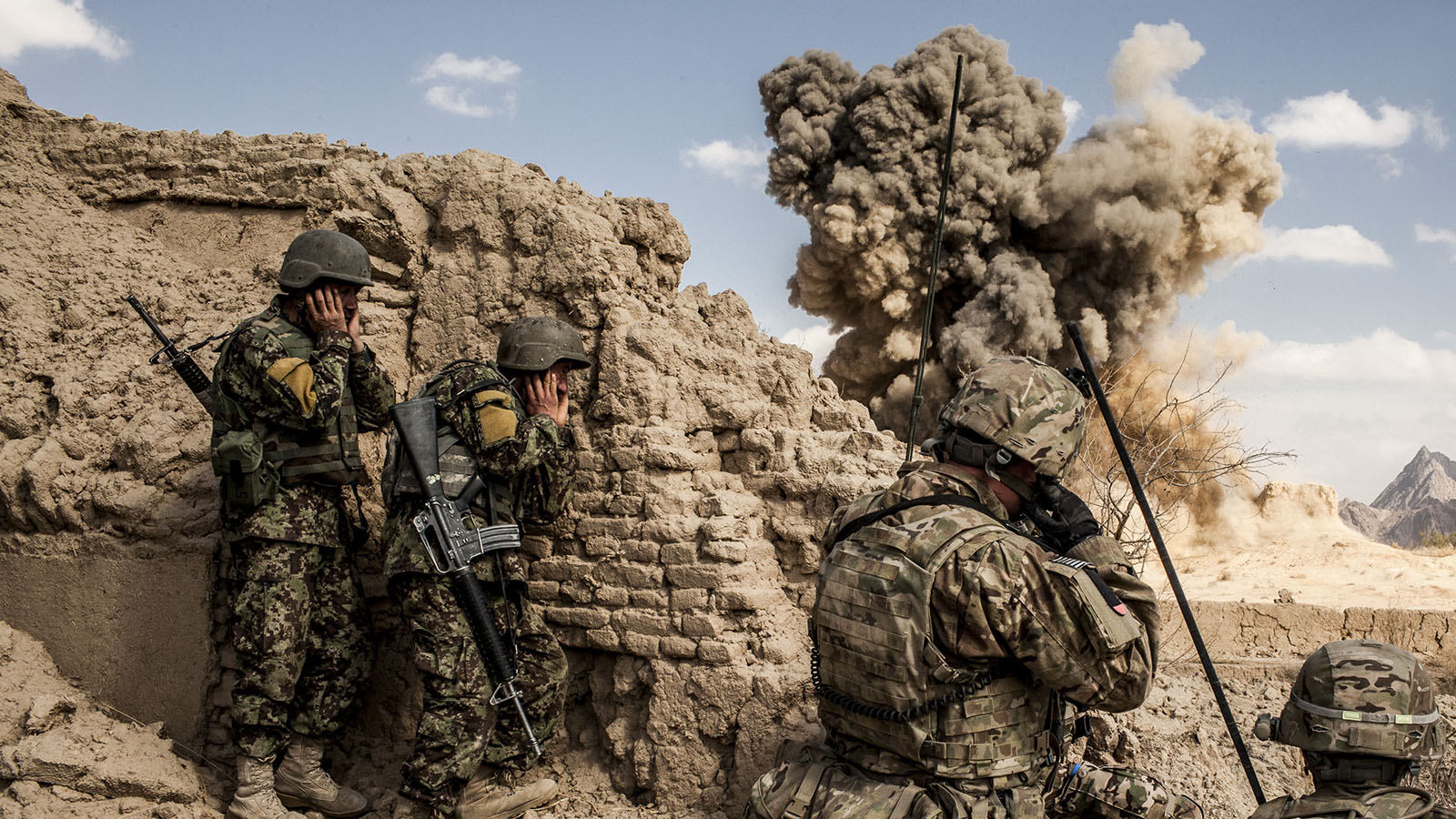 Afghan National Army soldiers, left, and American soldiers from Bravo Company, 3rd Battalion, 1st Armored Division, destroy a Taliban firing position in the Layadira village of Kandahar province, Afghanistan, Feb. 14, 2013. As American troops prepare to speed up their 2014 withdrawal, it is clear some of it will happen under fire, as Taliban fighters try to strike at departing soldiers. (Bryan Denton/New York Times/Getty Images)