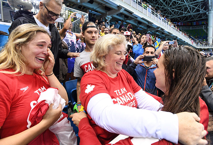 Canada's Penny Oleksiak, right, gets a hug from her mom following her gold-medal performance at the women's 100m freestyle finals during the 2016 Olympic Summer Games in Rio de Janeiro, Brazil, on Friday, Aug. 12, 2016. (Sean Kilpatrick/CP)