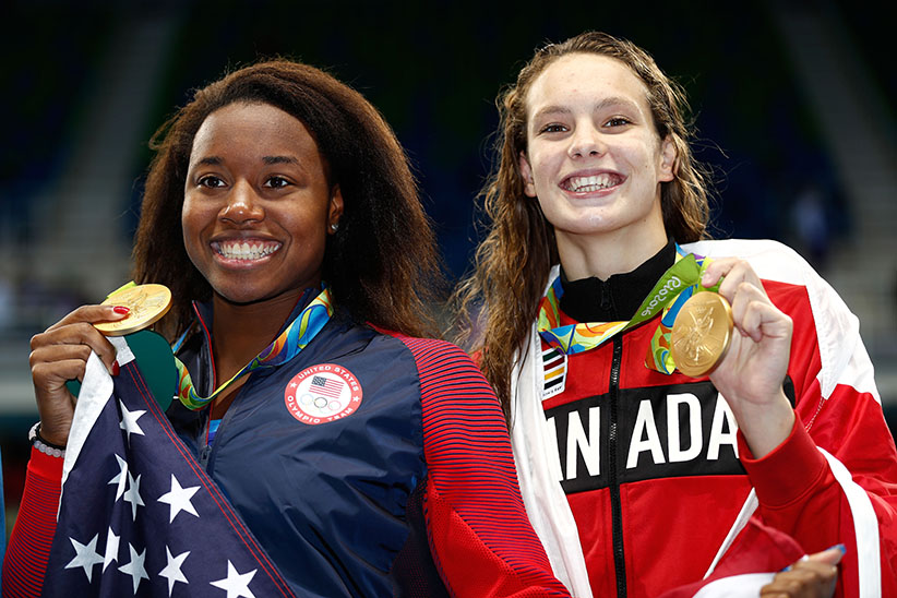 Gold medalist Simone Manuel of the United States (L) and gold medalist Penny Oleksiak of Canada celebrate during the medal ceremony for the Women's 100m Freestyle Final on Day 6 of the Rio 2016 Olympic Games at the Olympic Aquatics Stadium on August 11, 2016 in Rio de Janeiro, Brazil. (Clive Rose/Getty Images)