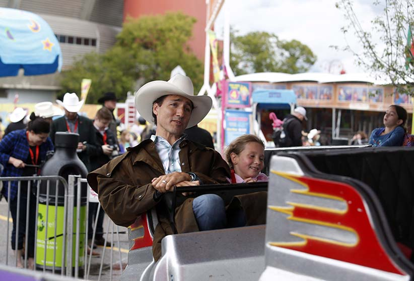 Prime Minister Justin Trudeau and his daughter Ella-Grace enjoy a ride during their visit to the Calgary Stampede, in Calgary on Friday, July 15, 2016. (Jeff McIntosh/CP)
