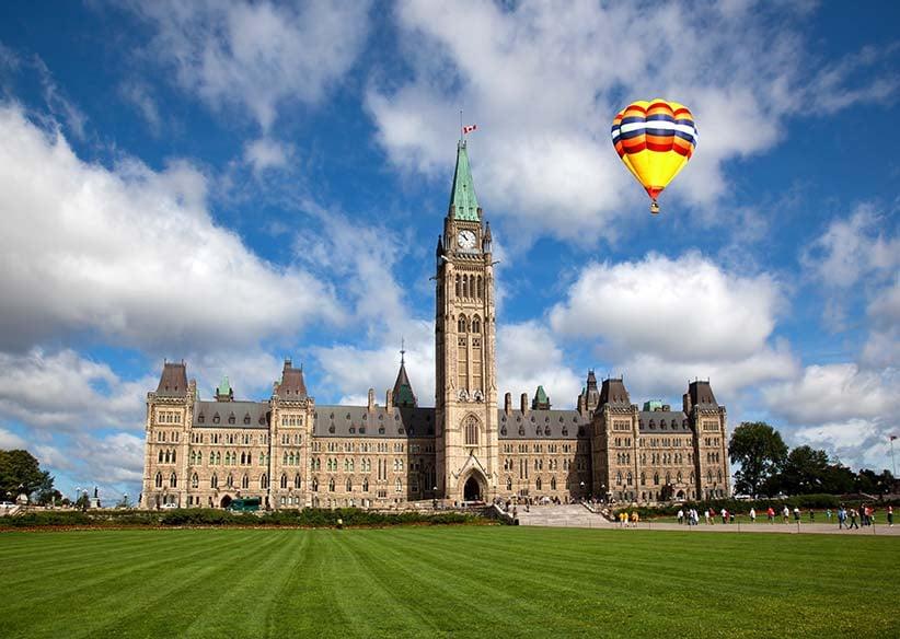 A hot air balloon in the distance ofof Parliament Hill in Ottawa. (Shutterstock)