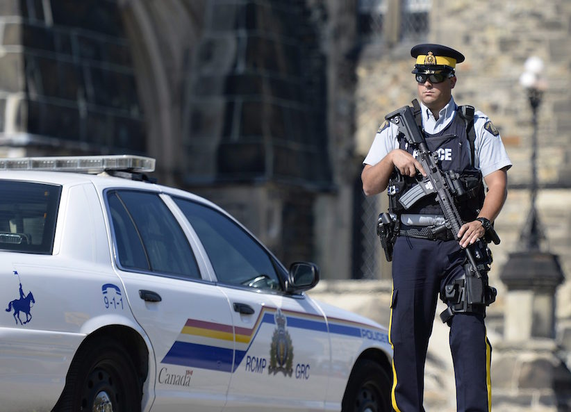An armed RCMP officer stands on Parliament Hill, a day after an RCMP incident involving Aaron Driver in Strathroy, Ontario, on Thursday, Aug. 11, 2016 in Ottawa. THE CANADIAN PRESS/Justin Tang
