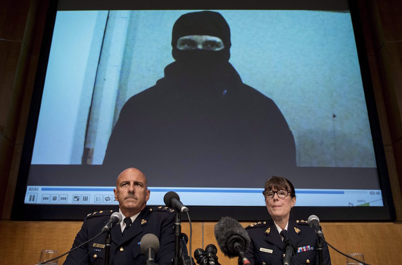 Video footage showing Aaron Driver is seen behind RCMP Deputy Commissioner Mike Cabana (left) and Assistant Commissioner Jennifer Strachan during a press conference for what the RCMP are calling a terrorism incident, in Strathroy, Ontario yesterday, on Thursday, Aug. 11, 2016 in Ottawa. THE CANADIAN PRESS/Justin Tang