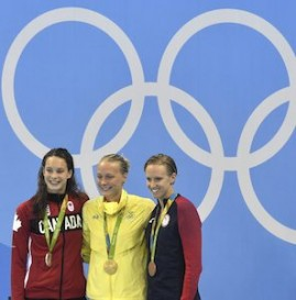 Sweden's gold medal winner Sarah Sjostrom is flanked by Canada's silver medal winner Penny Oleksiakand, left, and United States' bronze medal winner Dana Vollmer during the medal ceremony for the women's 100-meter butterfly final at the swimming competitions at the 2016 Summer Olympics, Sunday, Aug. 7, 2016, in Rio de Janeiro, Brazil. (AP Photo/Martin Meissner)