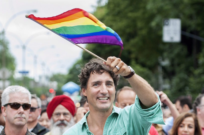 Prime Minister Justin Trudeau waves the rainbow flag as he attends the annual pride parade in Montreal, Sunday, August 14, 2016. THE CANADIAN PRESS/Graham Hughes