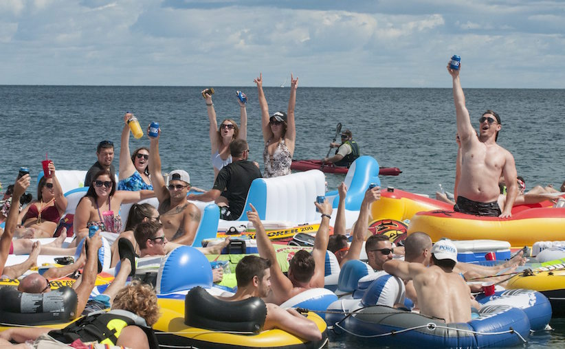 People celebrate as they start the Float Down at Lighthouse Beach in Port Huron, Mich., Sunday, Aug. 21, 2016. Thousands of people gathered for the event and floated down the St. Clair River. (Mark R. Rummel/The Times Herald via AP)
