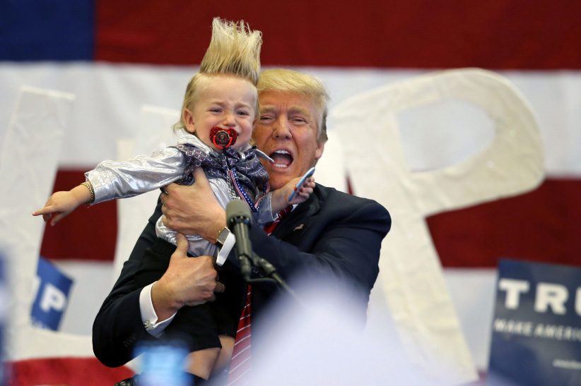 Republican presidential candidate Donald Trump holds up a child he pulled from the crowd as he arrives to speak at a campaign rally in New Orleans. (Gerald Herbert/AP)