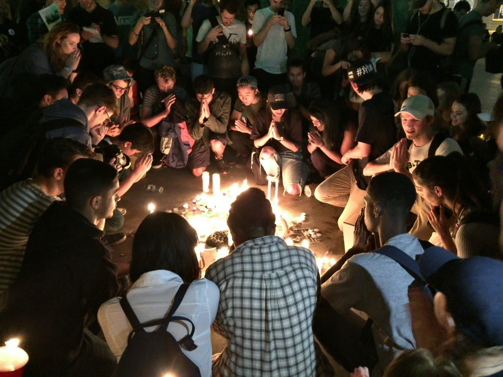 Students gather in a mock prayer to Harambe the gorilla at a candlelight vigil at Ryerson University in Toronto on September 22, 2016.