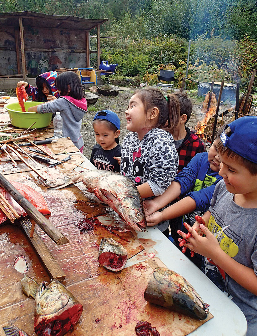 Ms. Wilson's Grade 1 class takes part in Salmon Week events (2015), learning how to prepare salmon for traditional barbecue around the fire. During Salmon Week, our students get hands-on experience with smoking, barbecuing, drying and jarring salmon. (Johanna Gordon-Walker)