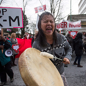 Patricia Kelly, of the Sto:lo First Nation, chants and beats a drum during a protest outside National Energy Board hearings on the proposed Trans Mountain pipeline expansion in Burnaby, B.C., on Tuesday January 19, 2016. The proposed $5-billion expansion would nearly triple the capacity of the pipeline that carries crude oil from near Edmonton to the Vancouver area to be loaded on tankers and shipped overseas. (Darryl Dyck)