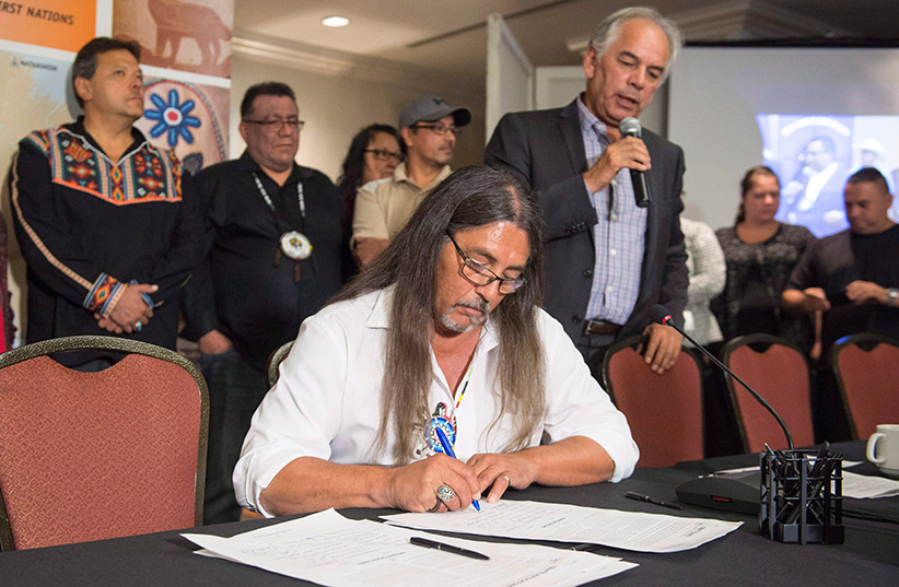 Serge Simon, Grand Chief of Kanesatake, signs a treaty as Ghislain Picard, Chief of the Assembly of First Nations of Quebec and Labrador, and other native leaders look on Thursday, September 22, 2016 in Montreal. Canadian First Nations and U.S. tribal communities have signed a treaty to fight the development and distribution of oilsands crude from Alberta. (Paul Chiasson/CP)