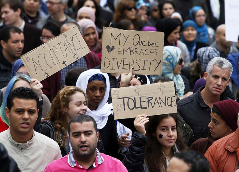 Demonstrators hold signs as they protest against Quebec's proposed Charter of Values in Montreal, September 14, 2013. Thousands took to the streets to denounce the province's proposed bill to ban the wearing of any overt religious garb by government paid employees. (Christinne Muschi/Reuters)
