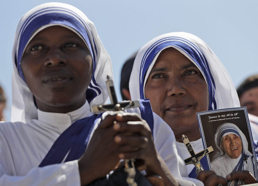 A Missionaries of Charity nun holds a photo of Mother Teresa in St. Peter's Square at the Vatican during a jubilee audience for workers and volunteers of mercy led by Pope Francis, Saturday, Sept. 3, 2016. The square hosts a ceremony Sunday expected to draw hundreds of thousands of admirers of Mother Teresa, a nun who before her death in 1997, cared for the destitute who were dying in the streets of India. (AP Photo/Alessandra Tarantino)