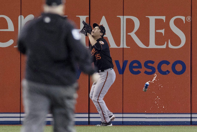 Baltimore Orioles' Hyun Soo Kim gets under a fly ball as a beer can sails past him during seventh inning American League wild-card game action against the Toronto Blue Jays in Toronto, Tuesday, Oct. 4, 2016. THE CANADIAN PRESS/Mark Blinch
