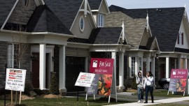 People walk past new homes that are for sale in Oakville, Ont. THE CANADIAN PRESS/Nathan Denette