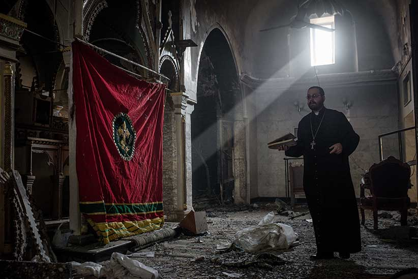 A Christian priest walks through debris in a partially destroyed church in Bartella, Iraq on October 23, 2016. (Photograph by Cengiz Yar)
