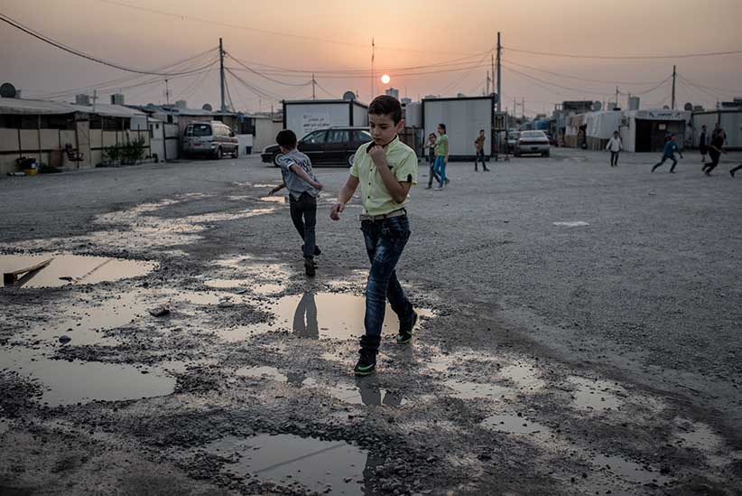 A child walks to church at a camp for displaced Christians in the Ankawa neighborhood of Erbil, Iraq on October 23, 2016. (Photograph by Cengiz Yar)