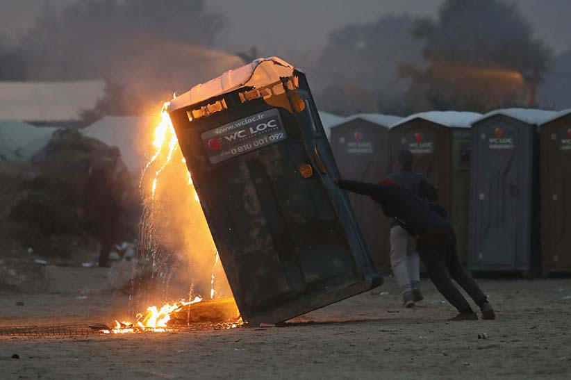 A migrant sets fire to a chemical toilet inside the Jungle camp on October 24, 2016 in Calais, France. Many migrants have left by coach to be reloctated at centres across France as Police and officials in France begin to clear the 'Jungle' migrant camp in Calais. Some 7,000 people are estimated to be living in the camp in squalid conditions.  (Christopher Furlong/Getty Images)