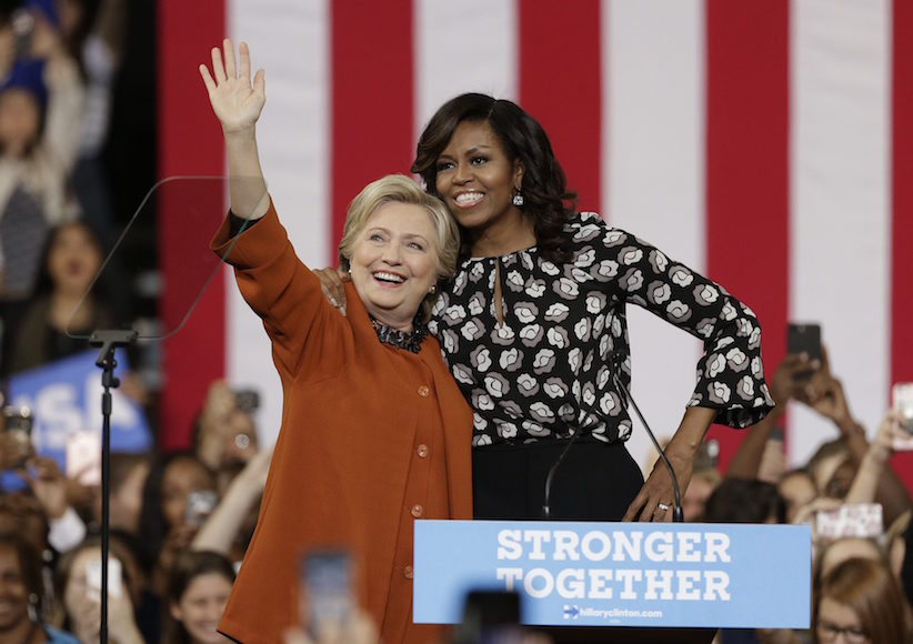 Democratic presidential candidate Hillary Clinton, accompanied by first lady Michelle Obama, greet supporters during a campaign rally in Winston-Salem, N.C., Thursday, Oct. 27, 2016. (AP Photo/Chuck Burton)