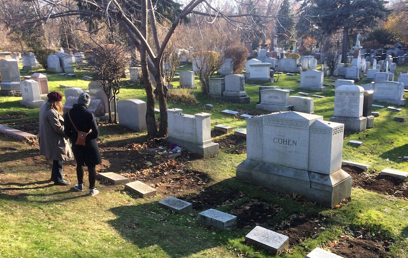 Two women stand at the grave of legendary singer and poet Leonard Cohen where he was buried Thursday at the family plot in the Shaar Hashomayim cemetery, in Montreal on Sunday, November 13, 2016. Cohen died last week at the age of 82. THE CANADIAN PRESS/Paul Chiasson