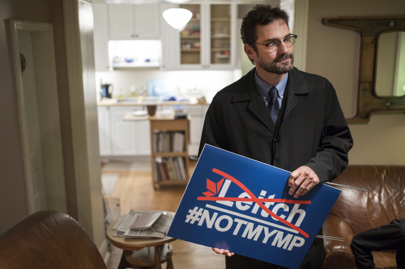 Mark Ruzylo holds a #NotMyMP sign in a neighbours home. (Photograph by Nick Iwanyshyn)