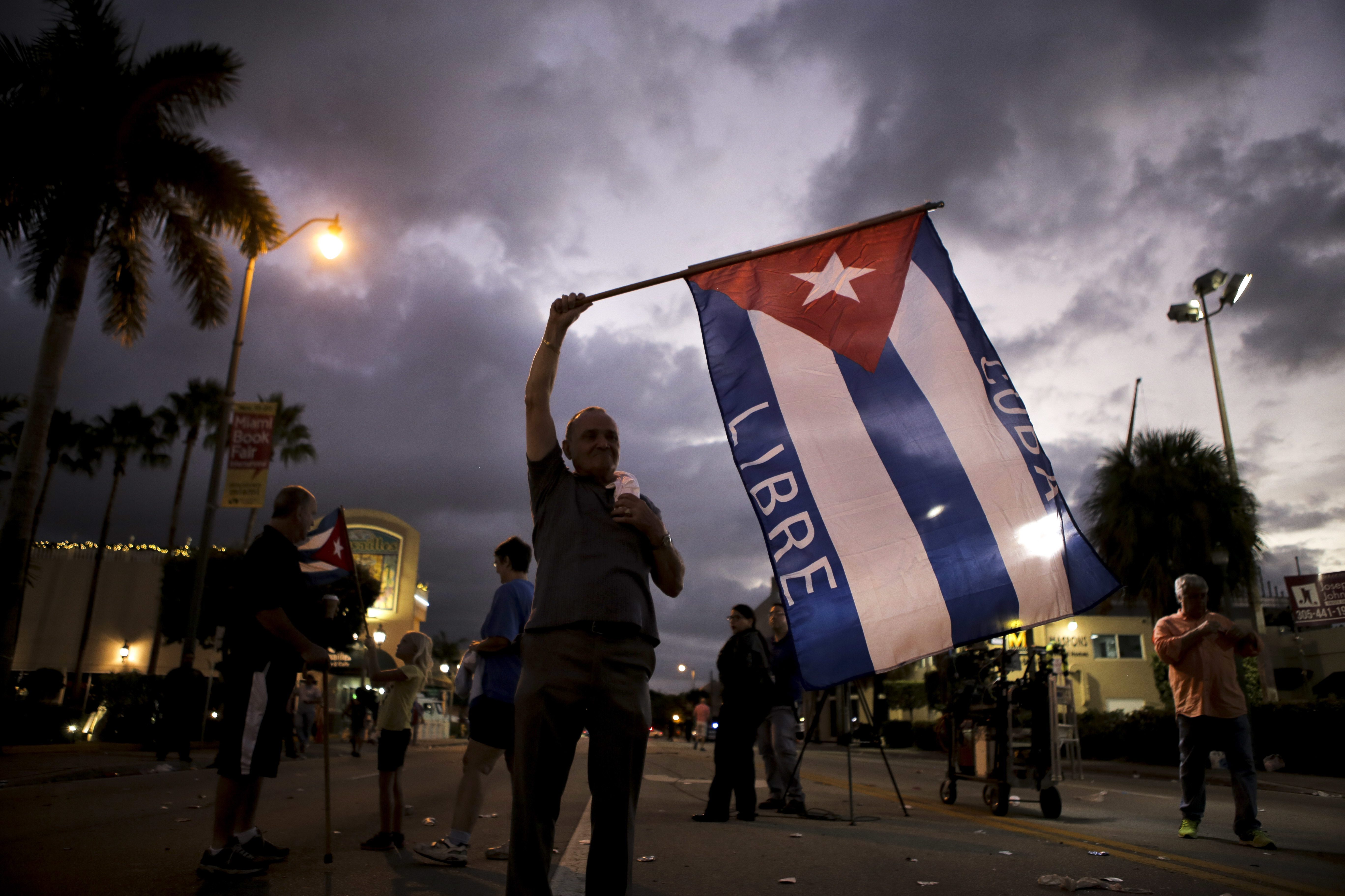 Hernan Reyes waves a Cuban flag on Saturday, nov. 26, 2016. Reyes was one of many people who celebrated the death of Fidel Castro in a festive way in the streets of Little Havana. Reyes described Saturday as the happiest day of his life. (Randy Vazquez/South Florida Sun-Sentinel via AP)