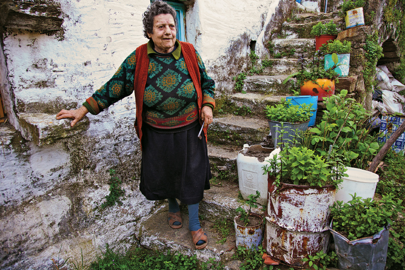 An elderly woman outside her home on Ikaria Island. Ikaria Island, Greece, April 16, 2009. (Gianluca Colla/National Geographic/Getty Images)