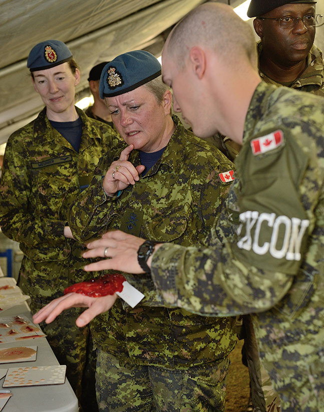 Captain Jordan MacKintosh demonstrates the moulage casualty make-up to Lieutenant-General Christine Whitecross and Lieutenant-Colonel Bethann Meunier during Exercise Collaborative CANUK at Canadian Forces Base Kingston on September 17, 2015. (Cpl Mark Schombs/DND)