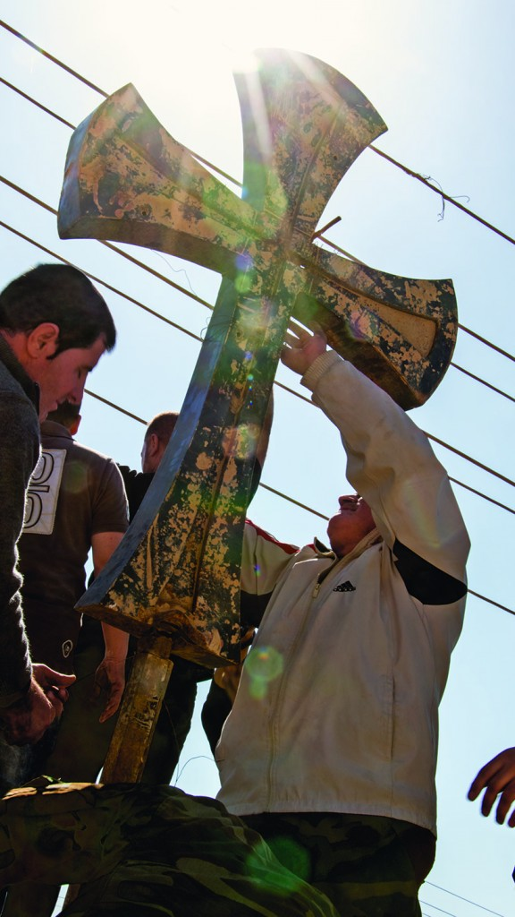 Local Christians replace the cross at the entrance to one of the churches in the predominantly Christian town of Qaraqosh. Islamic State has wreaked havoc in towns and villages during its retreat in northern Iraq. (Photograph by Adnan R. Khan)