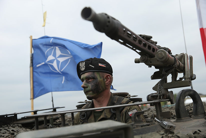 A soldier of the Polish Army sits in a tank as a NATO flag flies behind during the NATO Noble Jump military exercises of the VJTF forces on June 18, 2015 in Zagan, Poland. The VJTF, the Very High Readiness Joint Task Force, is NATO's response to Russia's annexation of Crimea and the conflict in eastern Ukraine. Troops from Germany, Norway, Belgium, Poland, Czech Republic, Lithuania and Belgium were among those taking part today.  (Sean Gallup/Getty Images)