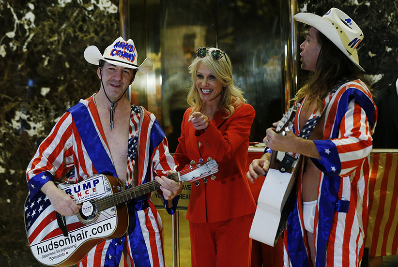"Kellyanne Conway, campaign manager and senior advisor to the Trump Presidential Transition Team, converses with ""Naked Cowboy"" themed street performers in the lobby at Trump Tower in New York, U.S., on Monday, November 28, 2016.  (Lucas Jackson/Reuters)"
