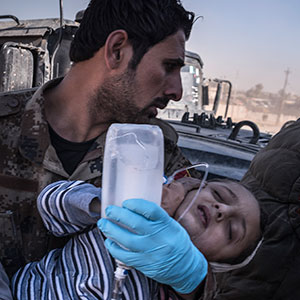 Medics carry a child wounded during fighting to a field hospital on the outskirts of Mosul, Iraq, Nov. 23, 2016. In the battle for Mosul, the last major stronghold of the Islamic State, civilians are paying a growing price, with more and more dead and wounded flowing out of the dense, urban battle zones each day. (Sergey Ponomarev/The New York Times/Redux)