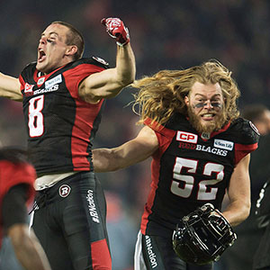 Ottawa Redblacks wide receiver Jake Harty (8) and Redblacks linebacker Tanner Doll (52) celebrate their victory over the Calgary Stampeders during overtime CFL Grey Cup action Sunday, November 27, 2016 in Toronto. (Nathan Denette/CP)