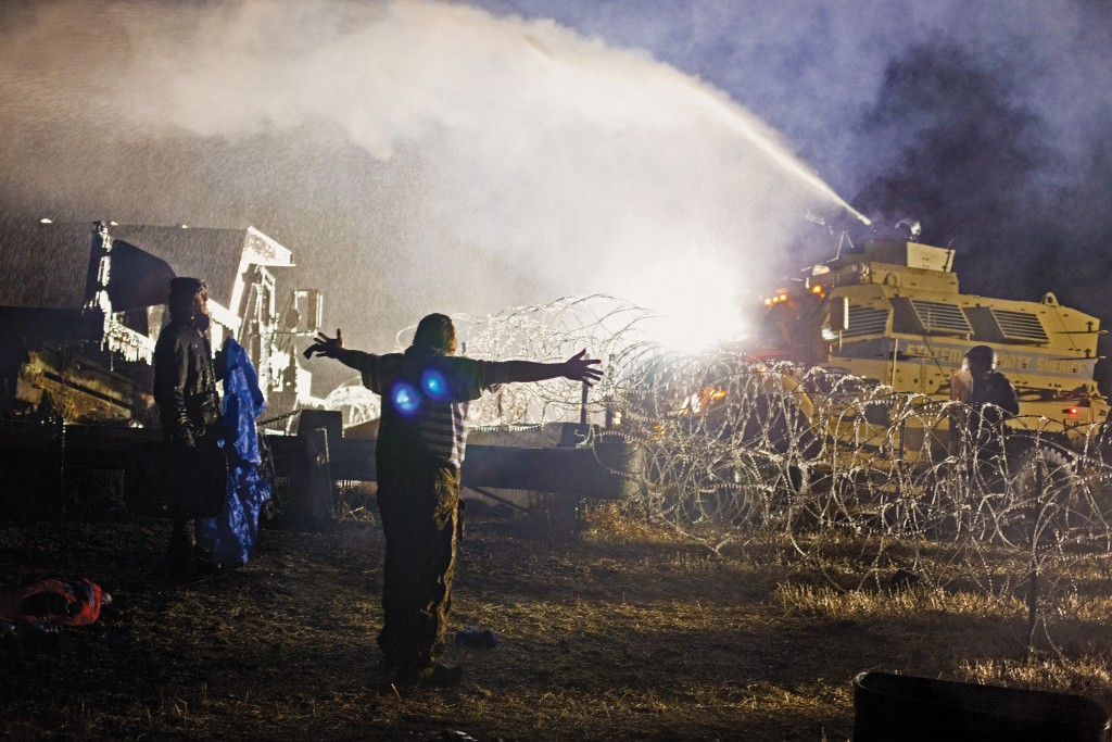 November 20, 2016: Protesters against the Dakota Access Pipeline are met by water cannons and a military response in Standing Rock. (Photograph by Amber Bracken)