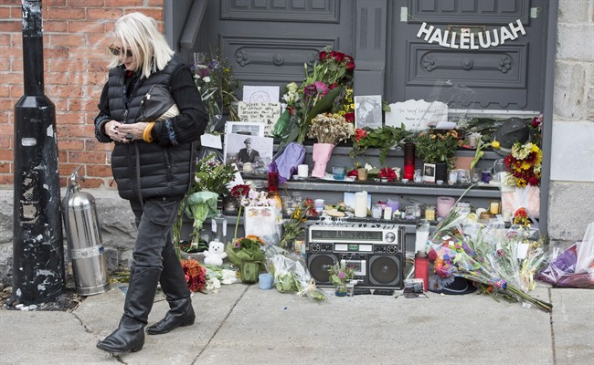 A woman walks away after placing flowers in front of the home of legendary singer and poet Leonard Cohen Friday, November 11, 2016 in Montreal. Cohen has died at the age of 82. THE CANADIAN PRESS/Paul Chiasson