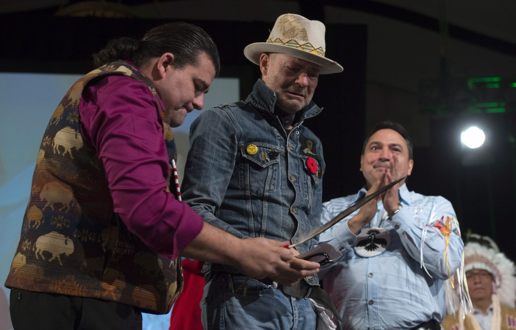 "Assembly of First Nations Chief Perry Bellegarde looks on as Lakota Sioux Donnie Speidel (left) honours singer Gord Downie with an eagle feather and name at the AFN Special Chiefs assembly in Gatineau, Que., Tuesday December 6, 2016. Downie was given the name ""The Man Who Walks Among the Stars,"" during the ceremony. THE CANADIAN PRESS/Adrian Wyld"