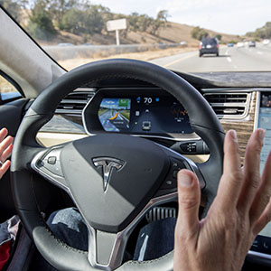 "A member of the media test drives a Tesla Motors Inc. Model S car equipped with Autopilot in Palo Alto, California, U.S., on Wednesday, Oct. 14, 2015. Tesla Motors Inc. will begin rolling out the first version of its highly anticipated ""autopilot"" features to owners of its all-electric Model S sedan Thursday. Autopilot is a step toward the vision of autonomous or self-driving cars, and includes features like automatic lane changing and the ability of the Model S to parallel park for you. (David Paul Morris/Bloomberg/Getty Images)"