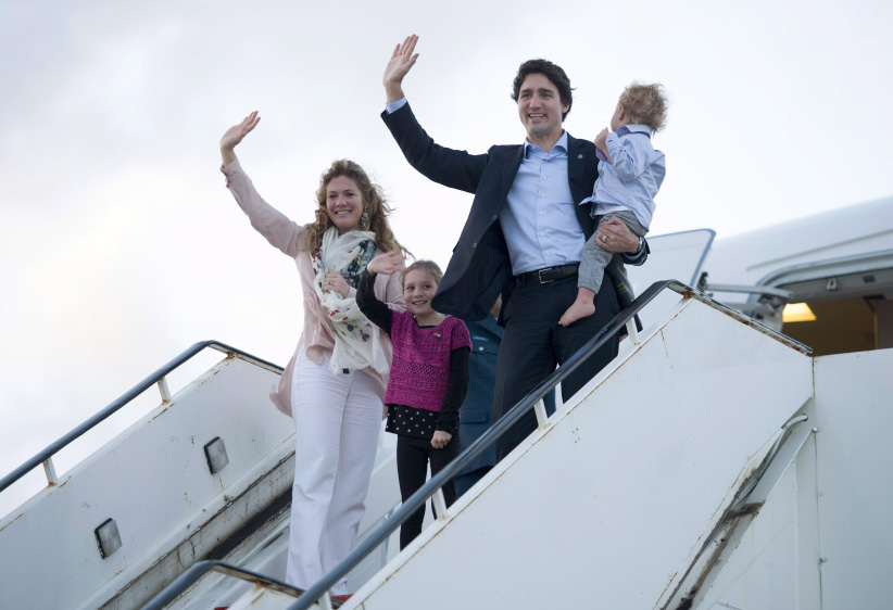 Canadian Prime Minister Justin Trudeau, Hadrien, Ella-Grace and his wife Sophie Gregoire-Trudeau board a government plane Saturday, November 28, 2015. (Adrian Wyld/CP)