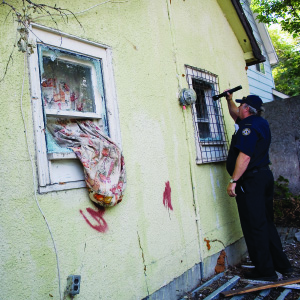 A Regina Fire Department official with the Housing Standards Enforcement Team looks into the window of an abandonned house in Regina's notorious North Central neighbourhood on August 24, 2006. Empty houses are often occupied by squatters for drug activity. (Photograph by Simon Hayter)