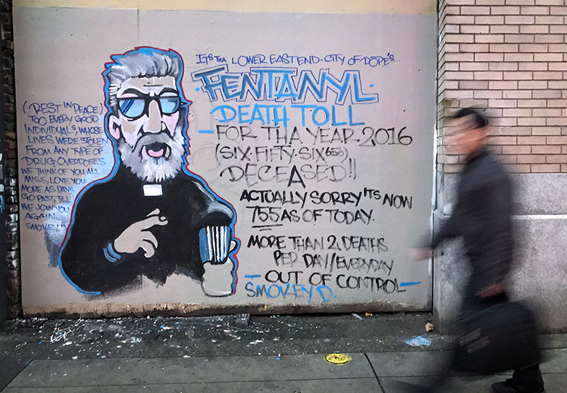 A man walks past a mural by street artist Smokey D. about the fentanyl and opioid overdose crisis, in the Downtown Eastside of Vancouver, B.C., on Thursday December 22, 2016. The number of overdose deaths related to illicit drugs in British Columbia leapt to 755 by the end of November, a more than 70-per-cent jump over the number of fatalities recorded during the same time period last year. The B.C. Coroners Service says the powerful opioid fentanyl remains present in a high number of the fatalities and was detected in 374 of the cases, or about 60 per cent of the deaths. (Darryl Dyck/CP)