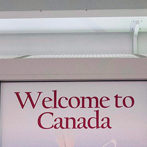A Canadian Border Services agent walks past a welcoming sign at Gate 521 at Pearson International Airport in Toronto. (Darren Calabrese/CP)