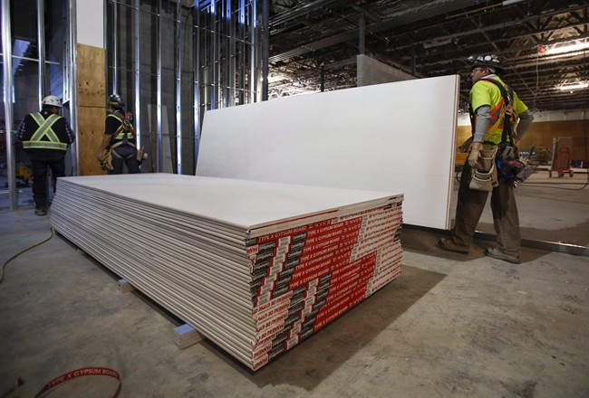 Construction workers move sheets of drywall at a building project in Calgary, Alta., Friday, Dec. 30, 2016. A decision expected later Wednesday could drive up the cost of rebuilding Fort McMurray after a wildfire swept through the northern Alberta city last spring. THE CANADIAN PRESS/Jeff McIntosh