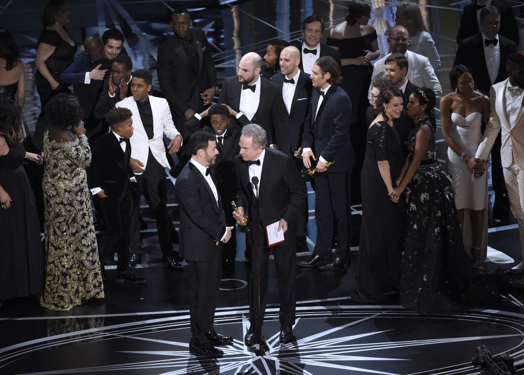"Host Jimmy Kimmel, left, and presenter Warren Beatty discuss the results of best picture as the casts of ""La La Land"" and ""Moonlight,"" winner of best picture, react on stage at the Oscars on Sunday, Feb. 26, 2017, at the Dolby Theatre in Los Angeles. (Photo by Chris Pizzello/Invision/AP)"