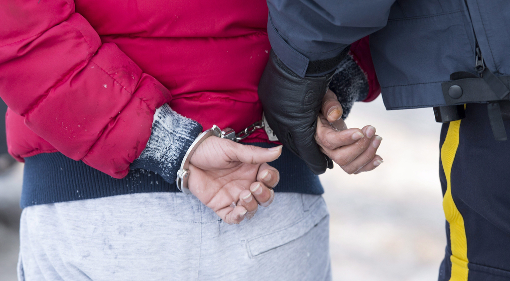 A young man from Yemen is handcuffed by an RCMP officer after crossing the U.S.-Canada border into Canada near Hemmingford, Que., on Friday, February 17, 2017. A number of refugee claimants are braving the elements to illicitly enter Canada. (Paul Chiasson/CP)