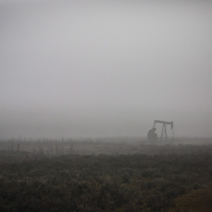 A pumpjack works at a well head on an oil and gas installation on a foggy day near Cremona, Alta., Saturday, Oct. 29, 2016. Oil and gas companies in Alberta are accelerating voluntary reclamation of old well sites and pipelines. (Jeff McIntosh/CP)