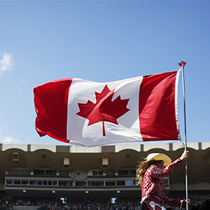 A Calgary Stampede rodeo girl carries the Canadian flag. (Todd Korol/Reuters)