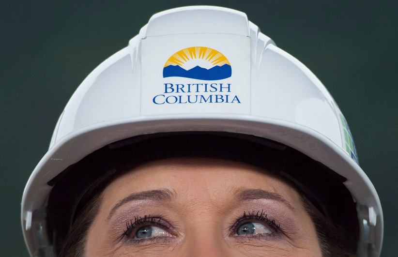 Wearing a hard hat, B.C. Premier Christy Clark listens to a question at the Woodfibre LNG project site near Squamish, B.C., on Friday November 4, 2016. (Darryl Dyck/CP)