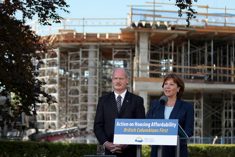 Premier Christy Clark and Finance Minister Michael de Jong, discuss amendments regarding housing issues in Greater Vancouver from the South lawn during a press conference at the Legislature in Victoria, B.C., Monday, July 25, 2016. (Chad Hipolito/CP)
