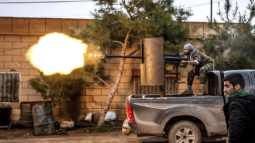 A fighter of the Kurdish People's Protection Units (YPG) fires an anti-aircraft weapon from Tel Tawil village in the direction of Islamic State fighters positioned in the countryside of the town of Tel Tamr February 25, 2015. (Rodi Said/Reuters)