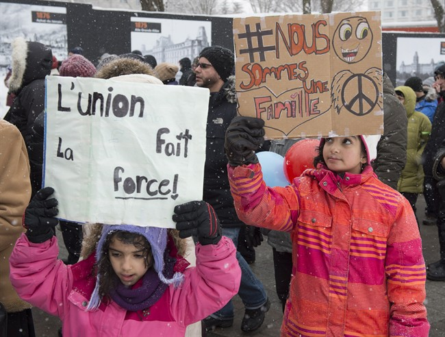 Seven-year-old Hajar Djilali-Merzoug, left, and her sister Affafe, of Saguenay Que., holds handmade signs at a march in solidarity to the victims of the mosque shooting, Sunday, February 5, 2017 in Quebec City. Six people died in a shooting at a Quebec City mosque on January 29. THE CANADIAN PRESS/Jacques Boissinot